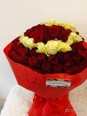 ανθοδέσμη με 101 τριαντάφυλλα κόκκινα και λευκά σε σχήμα καρδιάς στην μέση