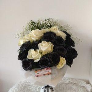 ασπρόμαυρη αμθοδέσμη με άσπρα και μαύρα τριαντάφυλλα τυλιγμένα με ύφασμα και μαύρη δαντέλα