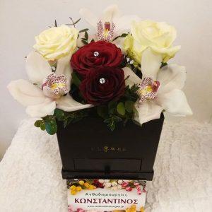 σύνθεση λουλουδιών σε τετράγωνο μαύρο κουτί μαζί με σοκολατάκια ferrero Rosher
